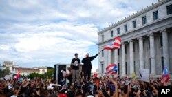 El rapero puertorriqueño René Juan Pérez, conocido como Residente, y Benito Antonio Martínez Ocasio, cuyo nombre artístico es Bad Bunny, animan a manifestantes frente al Capitolio antes de una marcha contra el gobernador Ricardo Rosselló, en San Juan, Puerto Rico.