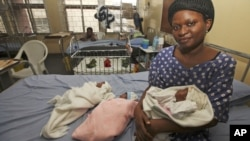 Mabel Ighedosa, 30, sits with her newborn triplets Isaac, Treasure and Samuel in a ward of the Lagos Island Maternity Hospital in Lagos, Nigeria, October 31, 2011.