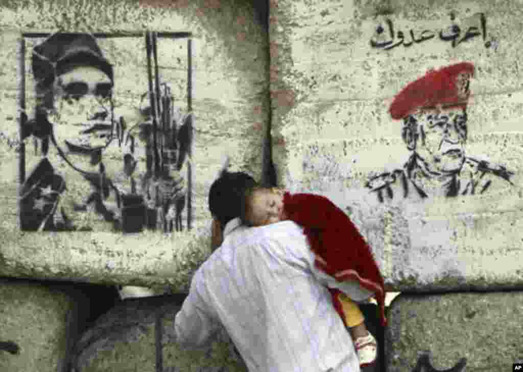 A man carries his child in front of barricades built by the Egyptian military at Mohamed Mahmoud street which leads to the Interior Ministry, where clashes between protesters and security force took place in late November, near Tahrir Square in Cairo Dece