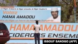 Un homme se tient devant une affiche de campagne du candidat présidentiel Hama Amadou à Niamey le 27 février 2016.
