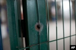 This April 12, 2017, photo shows a bullet hole on the front gate of a school in Acari, Rio de Janeiro, Brazil, where 13-year-old Maria Eduarda Conceicao was shot and killed when she was caught in the crossfire of a lengthy shootout between police and gangsters.