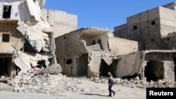 A man walks through damage and debris in Azaz village, north of Aleppo, Syria, March 30, 2014.