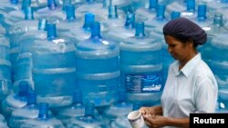 FILE - A woman walks past empty water containers at a water treatment plant in Colombo.