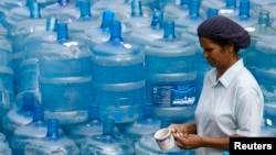 Una mujer pasa frente a recipientes de agua vacíos. La Tierra está cubierta de agua, pero el agua potable es cada vez más escasa.