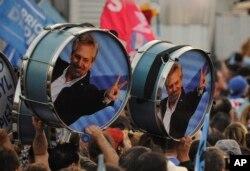 """Partidarios del candidato del Partido """"Frente de Todos"""" Alberto Fernández sostienen tambores decorados con su imágen un mitin en Rosario, Argentina, el miércoles, 7 de agosto, de 2019."""