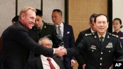 Acting U.S. Secretary of Defense Patrick Shanahan, left, shakes hands with Chinese Minister of National Defense Gen. Wei Fenghe on the sidelines of the 18th International Institute for Strategic Studies Shangri-la Dialogue, Singapore, June 1, 2019.