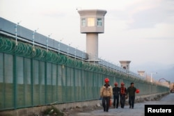 FILE - Workers walk by the perimeter fence of what is officially known as a vocational skills education center in Dabancheng in Xinjiang Uighur Autonomous Region, China,Sept. 4, 2018.