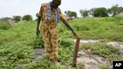 A government soldier inspects a rocket found after recent clashes with rebels in Kuek, northern Upper Nile state, South Sudan, Aug. 19, 2017.