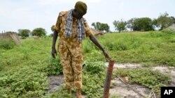 Un soldat du gouvernement inspecte une roquette découverte après des affrontements récents avec des rebelles à Kuek, dans le nord du Haut-Nil, Soudan du Sud, 19 août 2017.