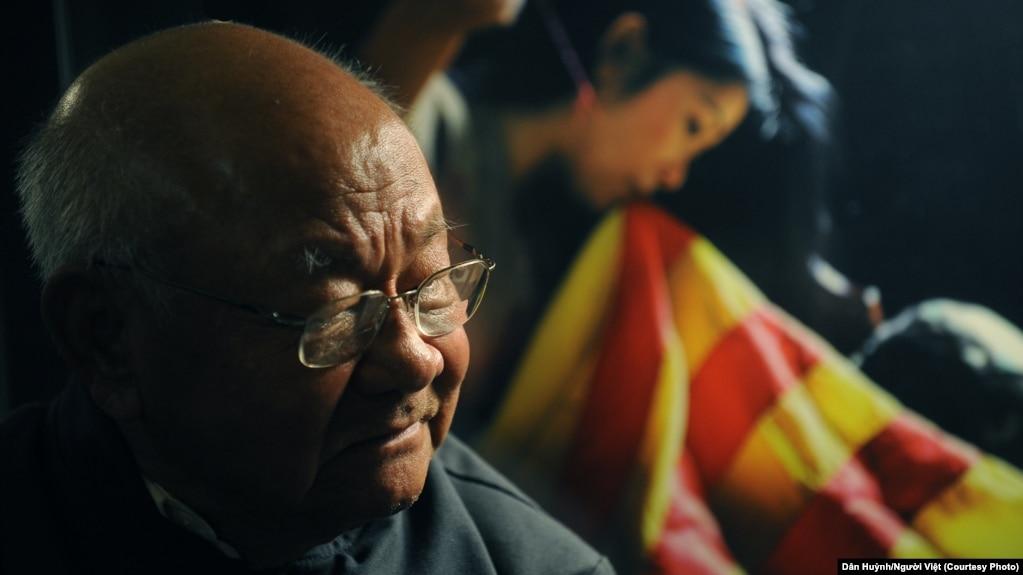 """Nhiếp ảnh gia Nguyễn Ngọc Hạnh và tác phẩm """"Vá Cờ."""" (Hình: Dân Huỳnh/Người Việt)"""