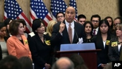 FILE - Sen. Cory Booker, D-N.J., center, speaks during a news conference on Capitol Hill in Washington, Jan. 30, 2018, about legislation to protect Deferred Action for Childhood Arrivals (DACA) program recipients.