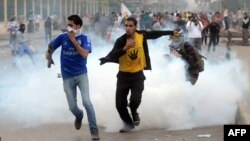 FILE - Supporters of ousted president Mohamed Morsi and the Muslim brotherhood run away from tear gas during clashes with Egyptian riot police close to Rabaa al-Adawiya square, Nov. 22, 2013.