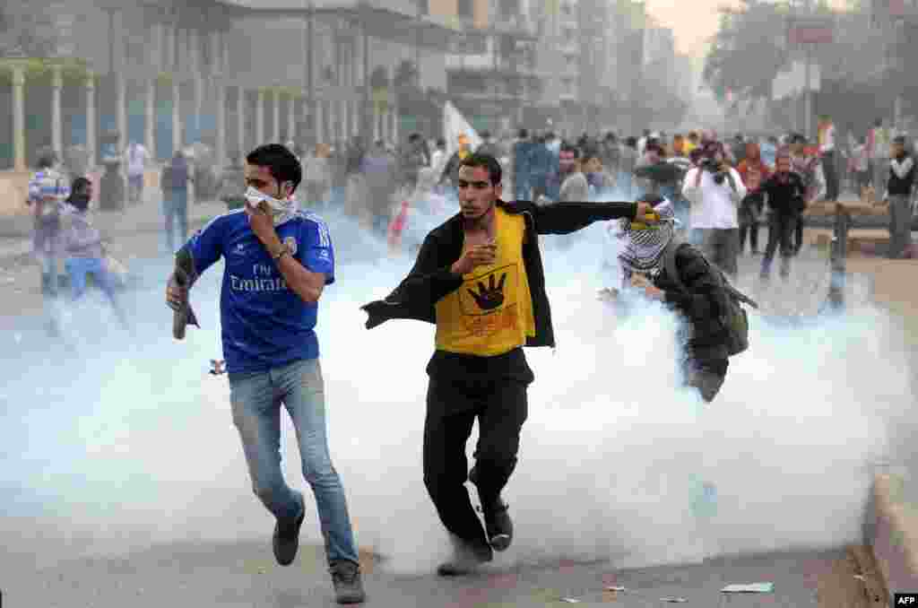 Supporters of ousted president Mohamed Morsi and the Muslim brotherhood run away from tear gas during clashes with Egyptian riot police close to Rabaa al-Adawiya Square.