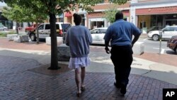 FILE - A woman who voluntarily went to the police for help kicking her heroin addiction walks from the police station for her ride to an area detox facility, in Gloucester, Massachusetts, July 10, 2015.