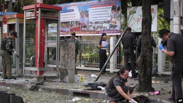 Police and forensic experts investigate the site where a man was injured when a bomb he was carrying exploded, in central Bangkok February 14, 2012.