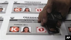 A worker inspects electoral ballots with images of presidential candidates in Lima, Peru, May 4, 2011