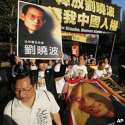 Pro-democracy protesters with banners bearing photos of jailed Chinese dissident Liu Xiaobo march to the Chinese government liaison office in Hong Kong, 05 Dec 2010