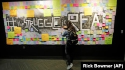 In this November 14, 2019, photo, a student attaches a note to the Resilience Project board on the campus of Utah Valley University, in Orem, Utah. The purpose of the project is to let students know that it is OK to struggle. (AP Photo/Rick Bowmer)