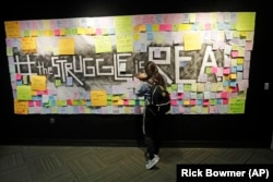 In this November 14, 2019, photo, a student attaches a note to the Resilience Project board on the campus of Utah Valley University, in Orem, Utah. The purpose of the project is to let students know that it is OK to struggle.
