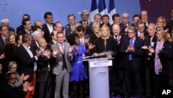 Far-right leader presidential candidate Marine Le Pen, center, stands among party officials at the end of a conference in Lyon, France, Sunday, Feb. 5, 2017.