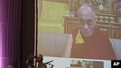 South African Archbishop Desmond Tutu, sitting at left, speaks during a live video link with Tibetan spiritual leader the Dalai Lama, on screen, near the city of Cape Town, South Africa, October 8, 2011.