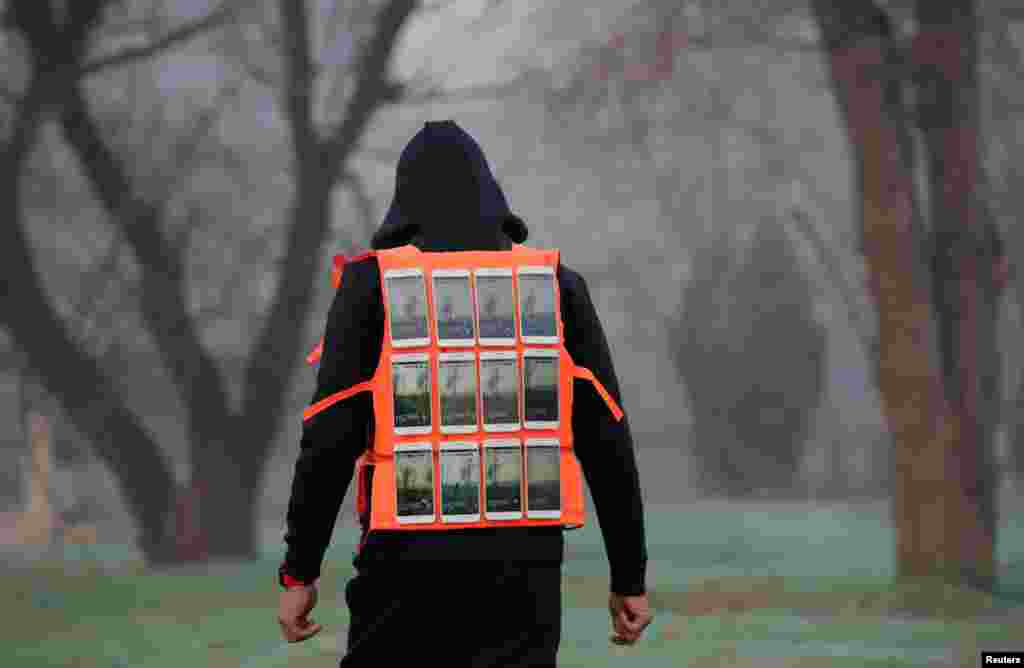 Artist Liu Bolin wearing a vest with 24 mobile phones walks in smog as he live broadcasts air pollution in the city on the fourth day after a red alert was issued for heavy air pollution in Beijing, China.