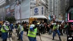 Para pekerja menyapu jalanan setelah pihak berwenang membongkar barikade dan tenda di jalanan utama district Causeway Bay, Hong Kong yang dikuasai para pengunjuk rasa (15/12).