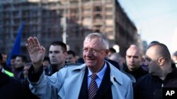 FILE - Serbian far right leader, Vojislav Seselj, center, waves to his supporters at a rally in Belgrade, Serbia, Nov. 15, 2014.