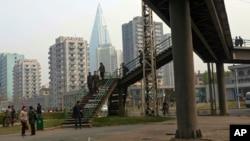 FILE - North Koreans walk on a pedestrian bridge in Pyongyang.