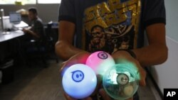 Examples of a remote-controlled ball toy called Sphero is held by an employee at Sphero, a fast-growing toy robotics company in Boulder, Colorado, July 24, 2015.