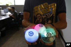 Examples of a remote-controlled ball toy called Sphero is held by an employee at Sphero in Boulder, Colorado, July 24, 2015.