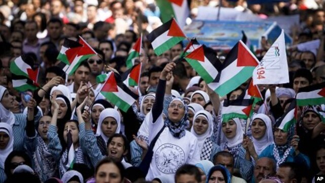 Palestinians wave flags during a rally in support of the Palestinian bid for statehood recognition in the United Nations, in the West Bank city of Ramallah, Sept. 21, 2011.