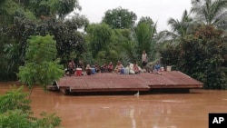 FILE - Villagers take refuge on a rooftop above flood waters from a collapsed dam in the Attapeu district of southeastern Laos, July 24, 2018.