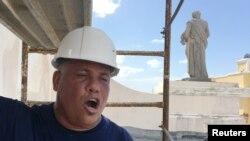 Jesus Santos sings operatic love songs while repairing plaster to a Hurricane Maria damaged facade at Cathedral of San Juan Bautista in San Juan, Puerto Rico on Oct. 4, 2017.