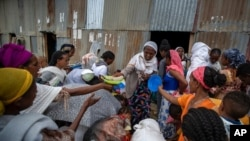 FILE - Displaced Tigrayans queue to receive food donated by local residents at a reception center for the internally displaced in Mekele, in the Tigray region of northern Ethiopia, May 9, 2021.