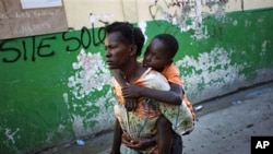 A boy suffering cholera symptoms is carried by a relative to St. Catherine hospital in Cite Soleil slum in Port-au-Prince, 18 Nov 2010