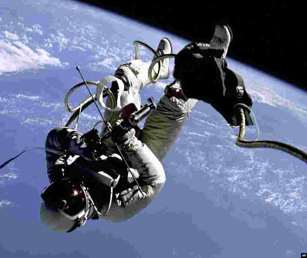 1965 Edward H. White II, pilot of the Gemini 4 spacecraft, floats in the zero gravity of space with an earth limb backdrop. This represents the first time an American has stepped outside the confines of his spacecraft. White is attached to the spacecraft