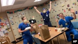 This photo provided by Brittney Caldera shows, from left to right, Oregon Health & Science University nurses Nick Greenwood, Callie Harling, Derrell Wheeler and Orion Meredith as they eat a meal delivered to the hospital's frontline COVID-19 health care workers in a break room.