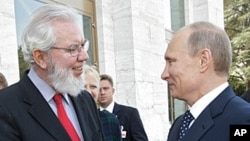 Juan Somavia, Director-General of the International Labor Organization, left, shakes hands with Russian Prime Minister Vladimir Putin at UN headquarters in Geneva, Switzerland, June 15, 2011.