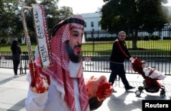 FILE- An activist dressed as Saudi Crown Prince Mohammad bin Salman marches in front the White House as another man pushes his child past in a stroller during a demonstration calling for sanctions against Saudi Arabia after the disappearance of Saudi journalist Jamal Khashoggi, in Washington, Oct. 19, 2018. It was determined that Khashoggi was killed Oct. 2 at the Saudi Consulate in Istanbul.