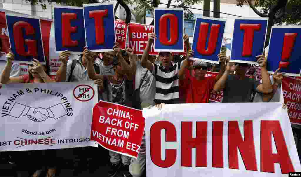 Philippine activists and Vietnamese nationals display placards and chant anti-China slogans as they march outside the Chinese consulate in Manila's Makati financial district, May 16, 2014.
