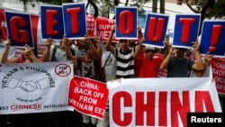 Filipino activists and Vietnamese nationals display placards and chant anti-China slogans as they march outside the Chinese Consulate in Manila's Makati financial district, May 16, 2014.