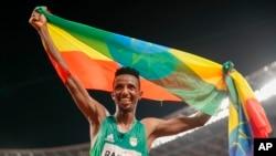Selemon Barega wa Ethiopia akishangilia na bendera ya nchi yake baada ya kutwaa medali ya dhahbu mita 10000.