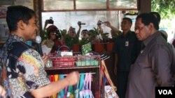 Menteri Negara Lingkungan Hidup Balthasar Kambuaya (kanan) melihat produk daur ulang di kampung iklim Yogyakarta. (Foto: VOA)