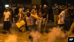 Seorang demonstran menendang kaleng gas air mata ke arah polisi dalam protes atas penembakan Michael Brown dekat Ferguson, Missouri (17/8).