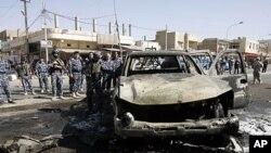 伊拉克警察8月15日在基尔库克检查炸弹爆炸现场