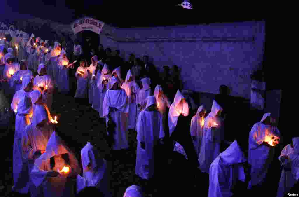 "Worshipers dressed in white tunics hold candles as they participate in the ""Procession of the Souls"" in the city of Mariana in the Brazilian state of Minas Gerais."