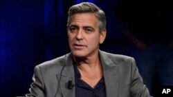 FILE - George Clooney is interviewed on Italy's RAI TV in Milan, Feb. 9, 2014.