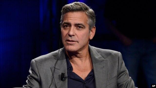 FILE - George Clooney is interviewed on Italy's RAI TV in Milan, Feb. 9, 2014.
