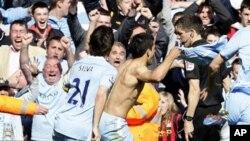 Sergio Aguero (tengah) merayakan gol penentu kemenangan Manchester City atas Queen Park Rangers hari Minggu (13/5)